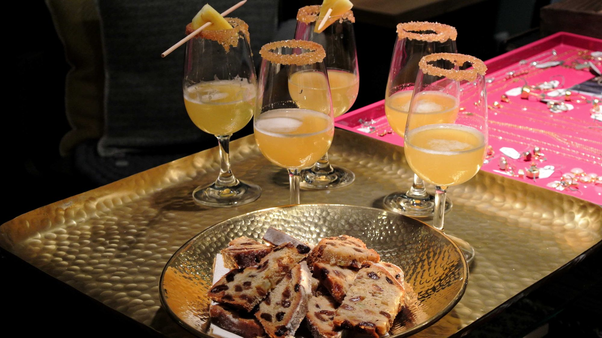 Dekorative Cocktailgläser mit Zuckerrand auf einem Messingtablett mit leckerem Christstollen.