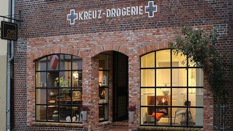 Die Aussenansicht des Stores in Garding zeigt das historische Gebäude der Kreuz - Drogerie mit den großen Industriefenstern und dem historischen Schriftzug