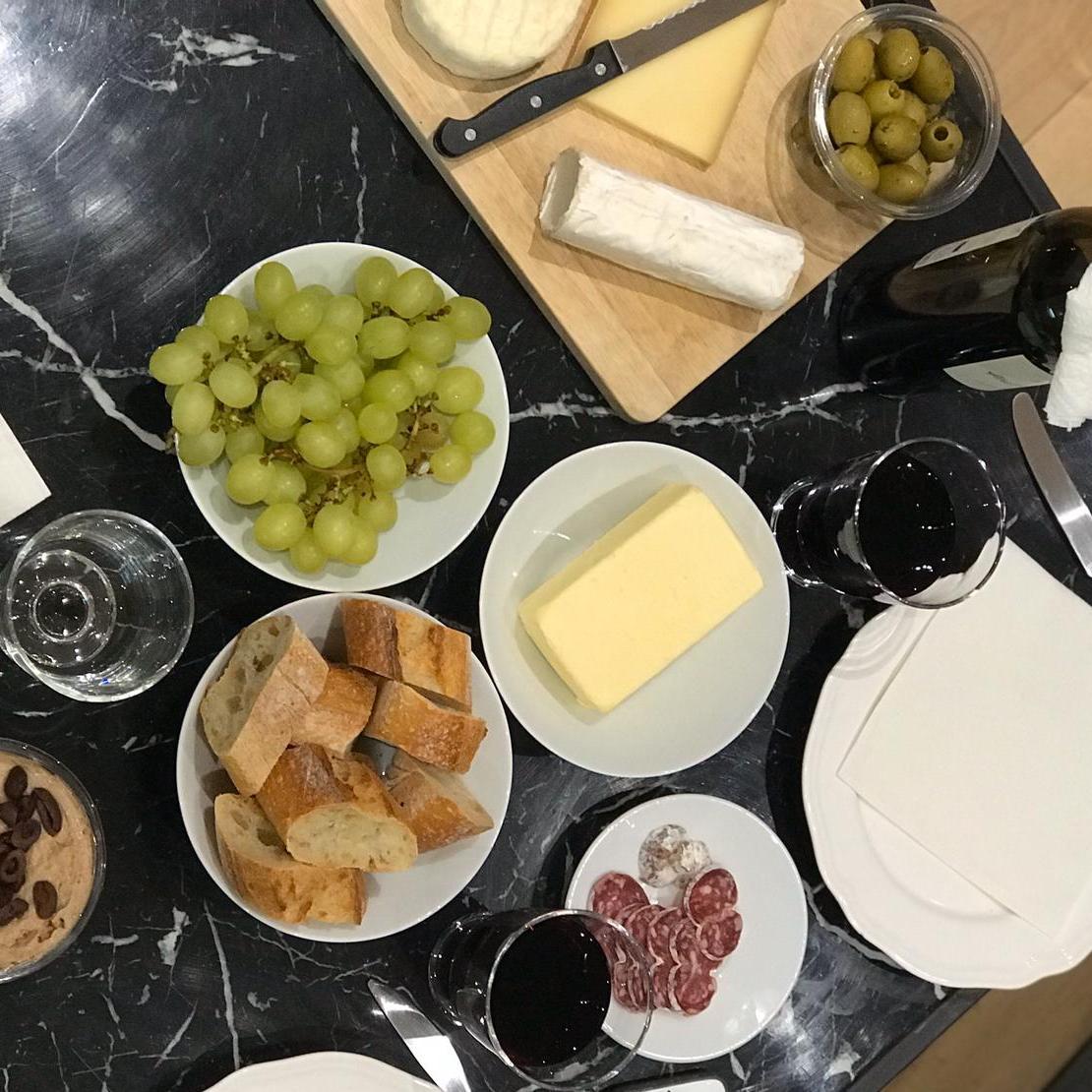 Ein tisch mit Salami, Baguette, Käse und Rotwein gedeckt