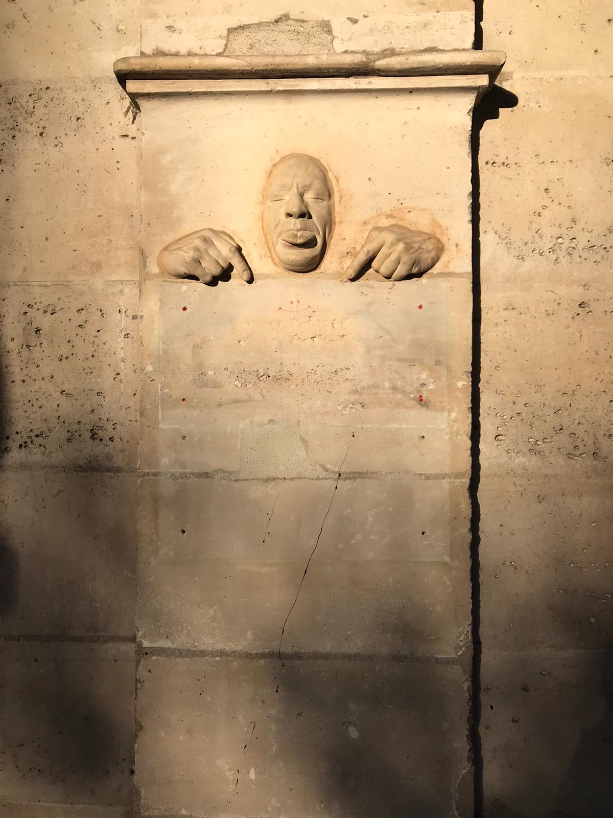 Ein Skulptur in einer Hauswand. Zwei Hände zeigen nach unten auf den Gehweg